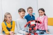 Fotografie usmívající se školáci pohledu na červené robota ručně na stole v kmenové třídě