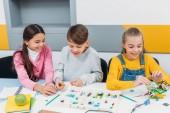 Fotografie šťastné děti sedí u stolu a konstrukci robota v kmenové třídě vzdělání