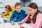 školáka a školačky psaní v poznámkových blocích a pomocí přenosného počítače během lekce stonku