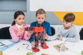 Fotografie concentrated schoolchildren constructing big red electric robot at desk during STEM lesson