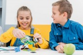Photo happy schoolchildren making robot with details in classroom