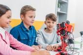 Fényképek mosolyogva nézett osztályteremben piros műanyag robot iskolás
