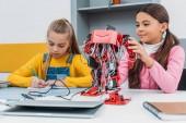 Fényképek notebook írásban és megható piros elektromos robot során szár lecke Diáklányok