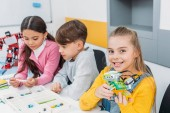 Photo smiling schoolgirl holding multicolored robot while classmates looking at box with details
