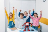Fotografie happy schoolchildren raising hands, smiling and looking at camera in stem class