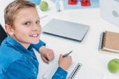 usměvavý chlapec psaní v poznámkovém bloku, s úsměvem a při pohledu na fotoaparát v kmenové třídě