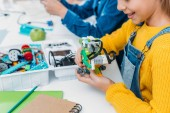 cropped view of schoolgirl building robot model at STEM class
