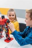 Photo smiling schoolchildren programming robot together during STEM educational class