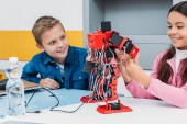 Photo adorable schoolgirl and smiling schoolboy sitting at desk and working together on robot model at STEM class