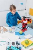 Fotografie šťastný kluk pracující na ruční robot modelu během lekce kmenových