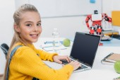 Fotografie smiling schoolgirl sitting at table with robot model, looking at camera and using laptop with blank screen during STEM lesson