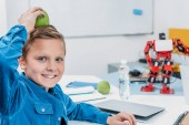 Fotografie cheerful schoolboy holding apple over head, looking at camera and having fun during STEM lesson