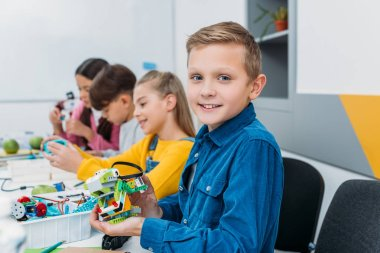 boy showing colorful robot during STEM robotics lesson