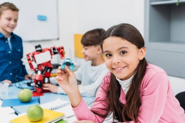 child shows robot detail at STEM robotics lesson