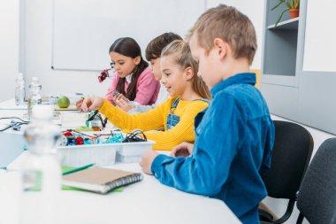 attentive schoolchildren assembling robot at STEM robotics lesson