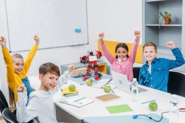 schoolchildren joying and raising hands at desk in stem education class