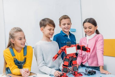 Smiling schoolchildren looking at red robot handmade on desk in stem class stock vector