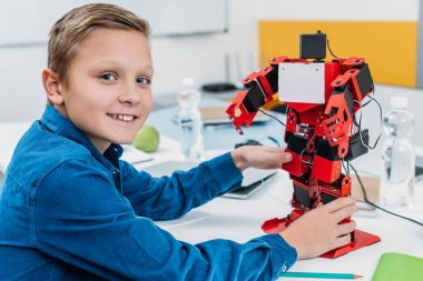 smiling boy holding red electric robot and looking at camera during stem lesson
