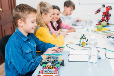 happy children sitting at desk and making robots in stem education class
