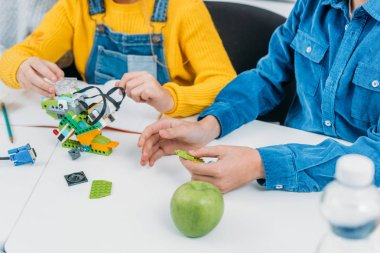 cropped view of schoolchildren making robot with details at desk in stem class