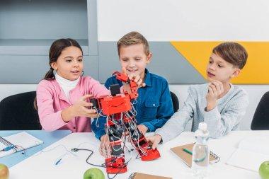 smiling schoolchildren building red electric robot during STEM lesson
