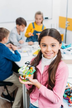 smiling schoolgirl holding robot and looking at camera with classmates at background