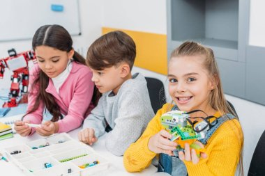 smiling schoolgirl holding multicolored robot while classmates looking at box with details