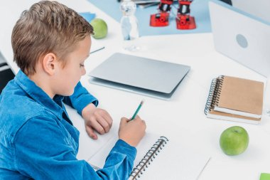 Schoolboy sitting at desk and writing on notebook in stem class stock vector