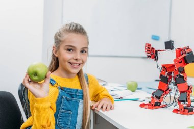 Smiling schoolgirl sitting at table with robot model at STEM classroom, holding apple and looking at camera stock vector