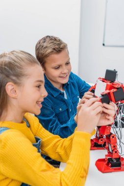 smiling schoolchildren programming robot together during STEM educational class