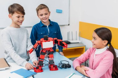 happy schoolchildren programming robot together during STEM educational class