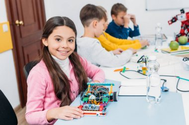 adorable schoolgirl holding robot model, looking at camera while classmates having STEM lesson