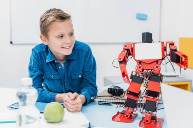 smiling schoolboy sitting at table and looking at robot model during STEM lesson