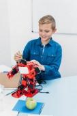 boldog iskolás kézzel robot modell dolgozik alatt szár lecke
