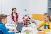 smiling schoolchildren programming robot together and using laptops during STEM educational class