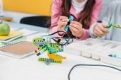 oříznutý pohled na spolužáky spolupracovat na projektu během lekce stonek s modelem ručně robota na popředí