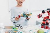 oříznutý pohled školák představí ruční robot model na stonku lekce