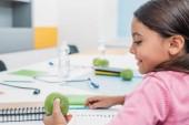 Fényképek Aranyos iskoláslány látszó-on Alma pultnál osztályteremben ülve