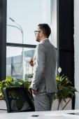 boční pohled podnikatel drží šálek kávy a při pohledu na okna v úřadu