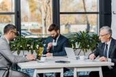 tři profesionální podnikatelé v oblasti formální oblečení, pracovat s digitálními zařízeními v úřadu
