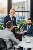 s úsměvem profesionální obchodníci, pití kávy a pracují společně v kanceláři