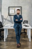 full length view of confident bearded businessman in suit and eyeglasses standing with crossed arms in office