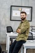 szép szakállas üzletember a szemüvegek karokkal ült és nézett kamera hivatalban