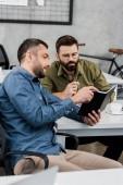 uomini daffari alla ricerca presso notebook e discutendo il progetto in ufficio
