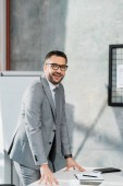 usměvavý pohledný podnikatel v obleku a brýle, opřel se o stůl a při pohledu na fotoaparát v úřadu