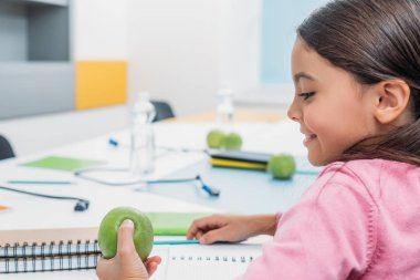 Adorable schoolgirl looking at apple while sitting at desk in classroom