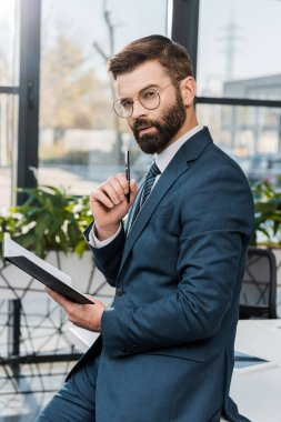 serious bearded businessman holding notepad and looking at camera in office