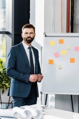 serious bearded businessman looking at camera while holding pen and standing near whiteboard