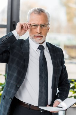confident mature businessman adjusting eyeglasses and looking at camera