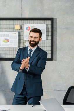happy bearded businessman applauding and smiling at camera in office